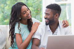 Happy couple on the couch using laptop Stock Image