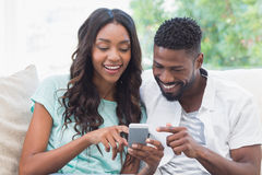 Happy couple on the couch using phone Stock Photos