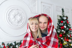 Happy couple covered with plaid. Family, Christmas. Holidays. Royalty Free Stock Photo