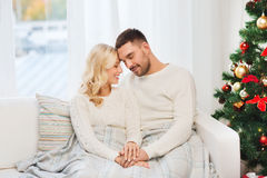 Happy couple covered with plaid on sofa at home Stock Photography