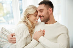 Happy couple covered with plaid on sofa at home Stock Image