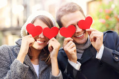 Happy couple covering eyes with hearts Stock Image