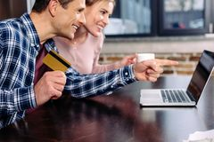 Happy couple with credit card and cup of coffee looking at laptop screen. At home royalty free stock image