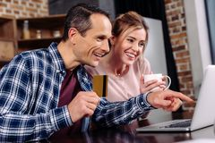 Happy couple with credit card and cup of coffee looking at laptop screen. At home stock image