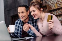 Happy couple with credit card and cup of coffee looking at laptop screen. At home royalty free stock photo