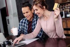 Happy couple with credit card and cup of coffee looking at laptop screen. At home royalty free stock photography