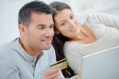 Happy couple with credit card and laptop at home. Young stock photos
