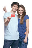 Happy couple with credit card. Happy couple in tshirts hugging, men showing blank credit card, women gesturing thumb up, on white background Royalty Free Stock Photos