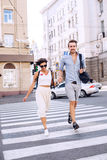 Happy couple crossing the street in city. At sunny day Stock Image
