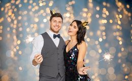 Happy couple with crowns and sparklers at party. Celebration, fun and holidays concept - happy couple with crowns and sparklers at party over festive lights stock photos