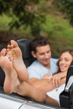 Happy couple cuddling in the backseat with focus on foot Stock Images