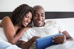 Happy couple cuddling in bed with tablet pc Stock Photography