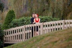 Happy Couple Cuddling on Bridge royalty free stock images