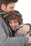 Happy couple cuddling each other with love. Happy young couple cuddling each other with love, dressed up warm, smiling royalty free stock photo