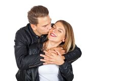 Happy couple cuddling and kissing. Happy young couple cuddling and kissing on isolated background Royalty Free Stock Image