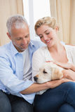 Happy couple cuddling with puppy on sofa Stock Images