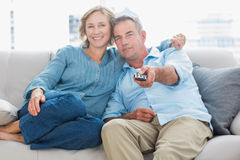 Happy couple cuddling and sitting on the couch watching tv. At home in the living room royalty free stock photography