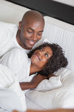 Happy couple cuddling together in bed Royalty Free Stock Photo