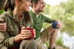 Happy couple with cups drinking in nature Royalty Free Stock Images