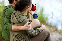 Happy couple with cups drinking in nature Stock Photography