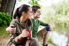 Happy couple with cups drinking in nature Stock Images