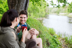 Happy couple with cups drinking in nature. Travel, tourism, hike, camping and people concept - happy couple with cups drinking tea in nature on river bank Royalty Free Stock Photo