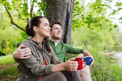 Happy couple with cups drinking in nature Royalty Free Stock Photos