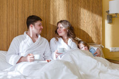 Happy couple with cups. Happy young family with cups of coffee lies on the bed in the room royalty free stock images
