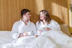 Happy couple with cups. Happy young family with cups of coffee lies on the bed in the room stock image