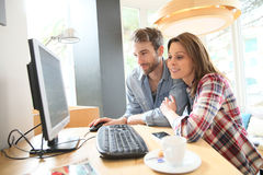 Happy couple in a cybercafe websurfing Royalty Free Stock Photography