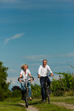 Happy couple cycling outdoors in summer Stock Images