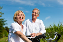 Happy couple cycling outdoors in summer Royalty Free Stock Images