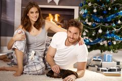 Happy couple with dachshund at christmas. Happy attractive young couple caressing sleeping dachshund puppy at christmas morning Stock Photography