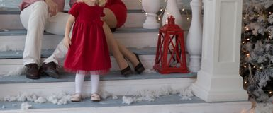 Happy couple, dad and mom are sitting on the stairs of the veranda, decorated house, Christmas. next to the child plays, a girl in royalty free stock photos