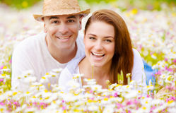 Happy couple on daisy field Stock Images