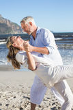 Happy couple dancing on the beach together stock photography