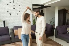 Happy young couple dancing in new home on moving day. Happy couple dancing in new home after moving in, smiling homeowners having fun packing boxes in living Royalty Free Stock Photography