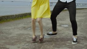 Happy couple dancing quickstep dance at the embankment. Energetic dance stock footage