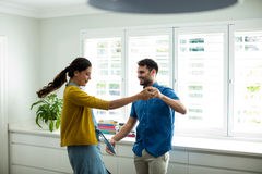 Happy couple dancing together in the kitchen Stock Image