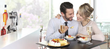 Happy couple date at the bar with wine and cake, love conc. Happy couple at the bar with wine and fruit cake, love concept Royalty Free Stock Image