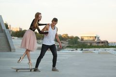 Happy couple on date. Young couple in love on a date. A guy sportsman teaches his girlfriend a ballerina to skateboard. Sports and dancing Royalty Free Stock Photo