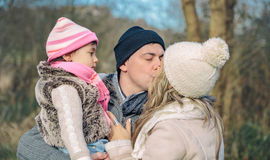 Happy couple with daughter kissing in the forest Royalty Free Stock Photo