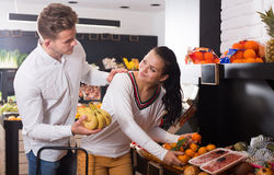 Happy couple deciding on fruits in shop. Happy couple deciding on fruits in grocery shop Royalty Free Stock Photography