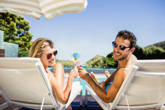 Happy couple on deck chair holding cocktails Stock Photography