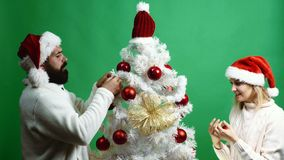 Happy couple decorates a Christmas tree on a green background. Bearded man and blonde women in New Year`s hats have fun. Spending time decorating Christmas tree stock footage