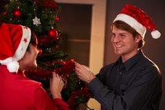 Happy couple decorating christmas tree Royalty Free Stock Images