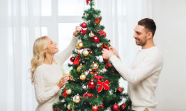 Happy couple decorating christmas tree at home Royalty Free Stock Photography