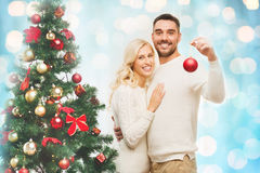Happy couple decorating christmas tree at home Royalty Free Stock Photo