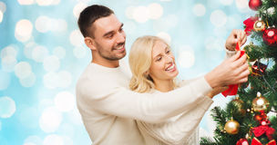 Happy couple decorating christmas tree at home Stock Photography