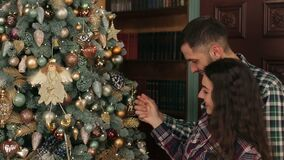 Happy couple decorating Christmas tree in home. stock footage